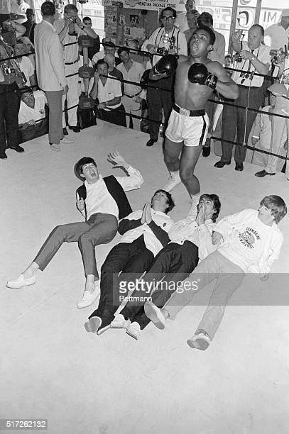 Heavyweight contender Cassius Clay stands above the Fab Four pounding his chest for photographers at his 5th Street gym The Beatles Paul John George...