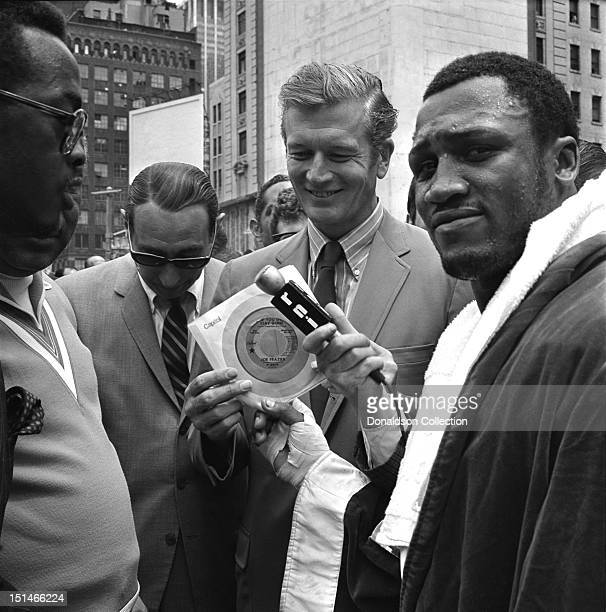 Heavyweight contender Joe Frazier hands his latest single 'If You go Stay Gone' to Mayor John Lindsey while Locke Edwards and Howard Cosell look on...