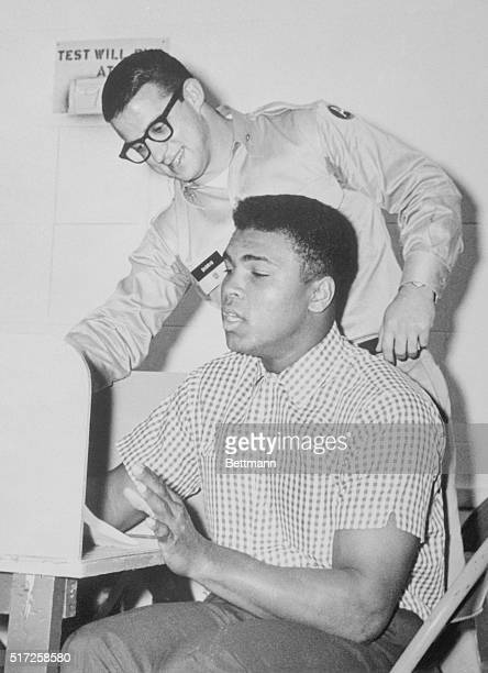 Heavyweight fighter Cassius Clay gets instructions from Lt. Reno Diorio at the Miami draft board 1/24 as Clay reported for pre-induction tests for...