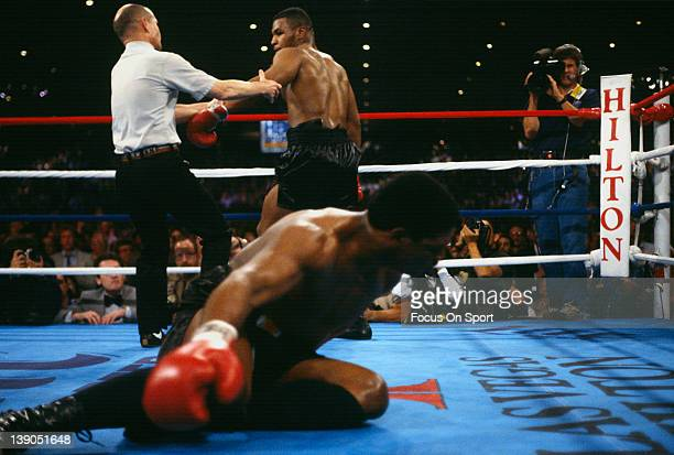 Heavyweight fighter Mike Tyson is sent to a neutral corner by referee Mills Lane after knocking down Trevor Berbick in the second round of a...