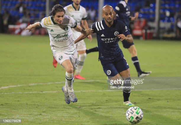 Heber of New York City fights for the ball with Jorge Villafana of Portland Timbers during a quarter final match of MLS Is Back Tournament between...