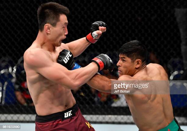 Hector Aldana of Mexico punches Song Kenan of China in their welterweight bout during the UFC Fight Night event at the Singapore Indoor Stadium on...