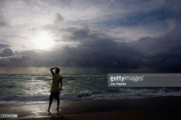 Hector Argueta holds his hat as he stands in the blowing winds while watching the swirling surf generated by Tropical Storm Ernesto August 30 2006 in...