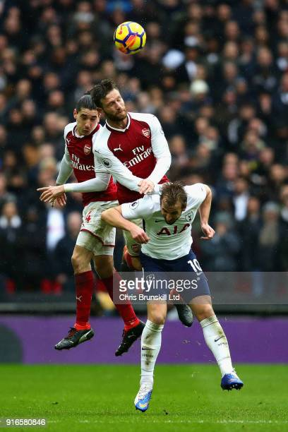Hector Bellerin and Shkodran Mustafi both of Arsenal challenge Harry Kane of Tottenham Hotspur for a header during the Premier League match between...