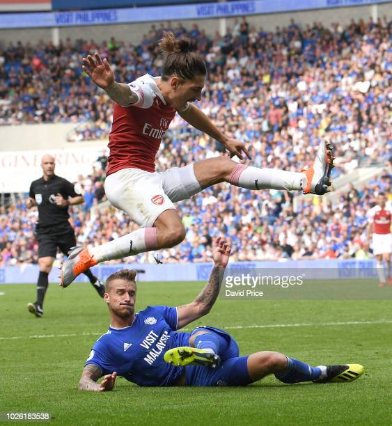 Hector Bellerin of Arsenal jumps the challenge from Joe Bennett during the Premier League match between Cardiff City and Arsenal FC at Cardiff City...