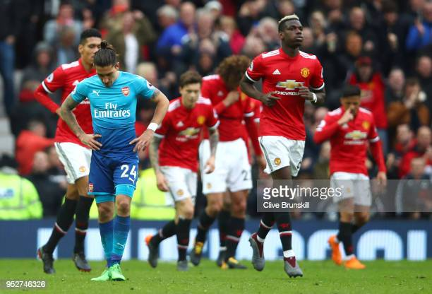 Hector Bellerin of Arsenal looks dejected as Paul Pogba of Manchester United runs back to the half way line after his side score their second goal...