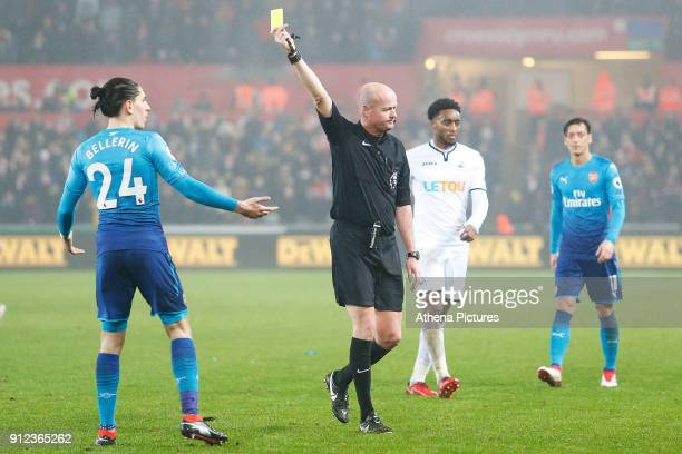 Hector Bellerin of Arsenal receives a yellow card from Referee Lee Mason during the Premier League match between Swansea City and Arsenal at the...