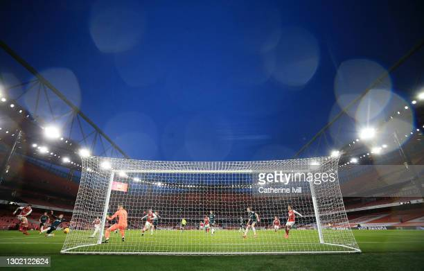 Hector Bellerin of Arsenal scores their side's third goal whilst under pressure from Ezgjan Alioski of Leeds United during the Premier League match...
