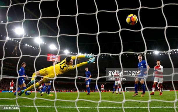 Hector Bellerin of Arsenal shoots past Thibaut Courtois of Chelsea to score his sides second goal during the Premier League match between Arsenal and...