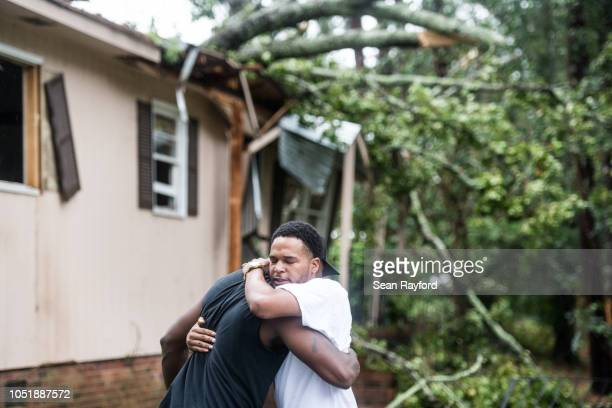 Hector Benthall right gets a hug from his neighbor Keito Jordan after remnants of Hurricane Michael sent a tree crashing into Benthall's home on...
