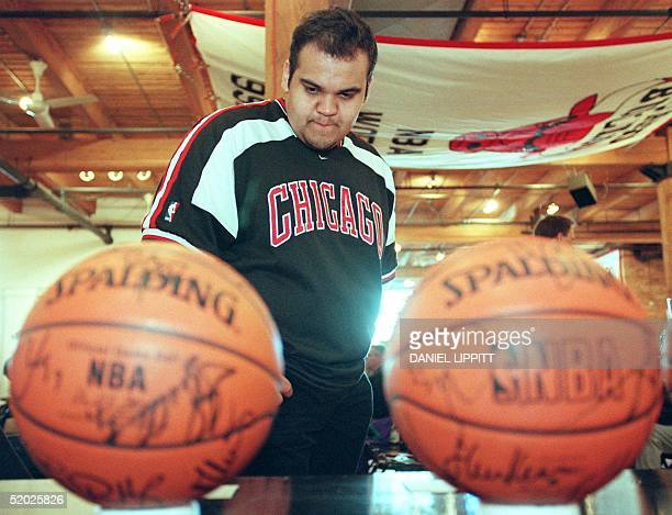 Hector Brambila of Chicago looks at two autographed Chicago Bulls game basketballs as he stands under the Chicago Bulls 9293 World Championship...