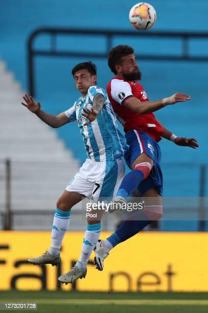 Hector Fertoli of Racing Club and Guzman Corujo of Nacional jump for a header during a group F match of Copa CONMEBOL Libertadores 2020 between...