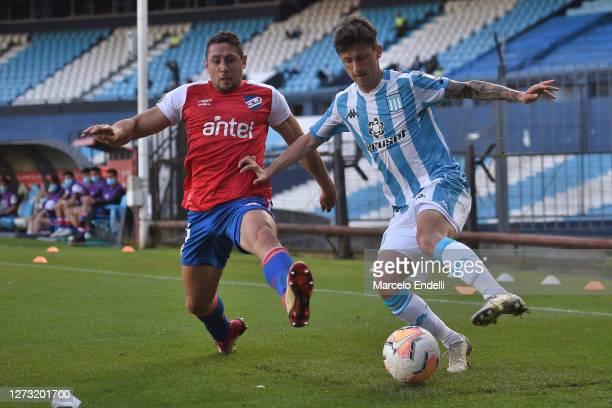 Hector Fertoli of Racing Club dribbles the ball past Armando Mendez of Nacional during a group F match of Copa CONMEBOL Libertadores 2020 between...