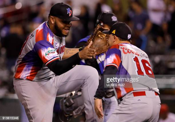 Hector Gomez and Junior Fermin of Aguilas Cibaenas of Republica Dominicana celebrate their victory against Alazanes del Granma of Cuba during the...
