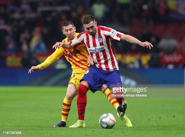 Hector Herrera of Atletico Madrid holds off Lionel Messi of FC Barcelona during the Liga match between Club Atletico de Madrid and FC Barcelona at...