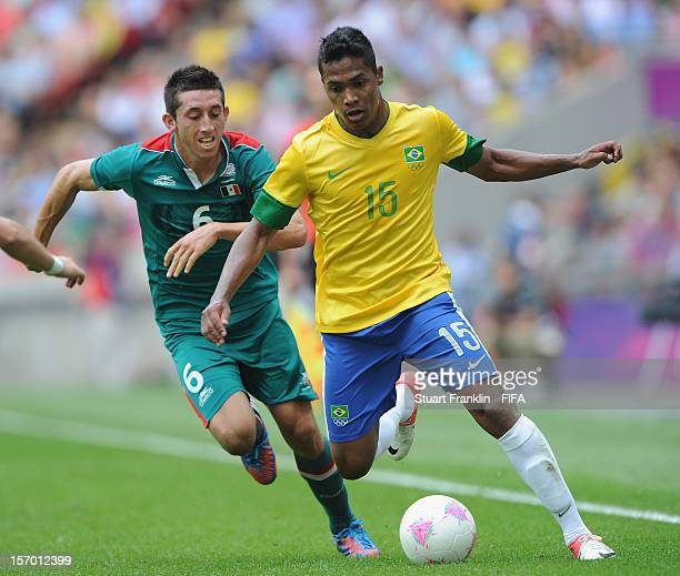 Hector Herrera of Mexico challenges for the ball with Alex Sandro of Brazil during the Men's Football Gold Medal match between Brazil and Mexico on...