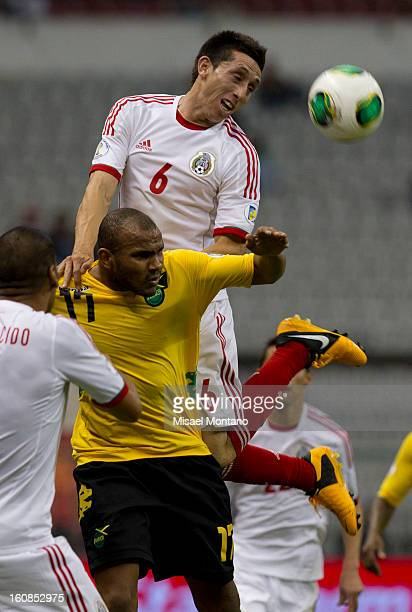 Hector Herrera of Mexico fights for the ball with Dane Richards of Jamaica during a match between Mexico and Jamaica as part of the CONCACAF...