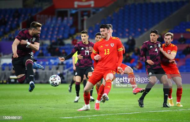 Hector Herrera of Mexico flicks a shot under pressure from Kieffer Moore of Wales during the International Friendly match between Wales and Mexico at...