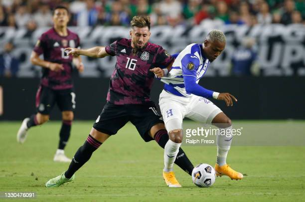 Hector Herrera of Mexico grabs the jersey of Deybi Flores of Honduras as they battle for contrl of the ball during the first half of the Concacaf...