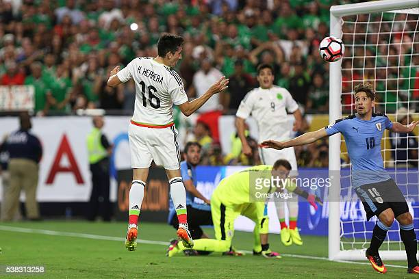 Hector Herrera of Mexico heads the ball to score the third goal of his team during the second half of a group C match between Mexico and Uruguay at...