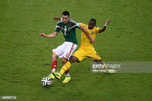 Hector Herrera of Mexico is challenged by Enoh Eyong of Cameroon during the 2014 FIFA World Cup Brazil Group A match between Mexico and Cameroon at...