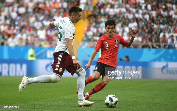 Hector Herrera of Mexico is challenged by Ju SeJong of Korea Republic during the 2018 FIFA World Cup Russia group F match between Korea Republic and...