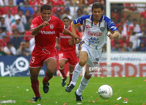 Hector Lopez of La Piedad runs with the ball while Carlos Maria Morales chases him during a match between Toluca and La Piedad as part of the Summer...