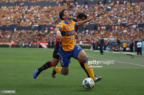 Hector Mancilla of Tigres struggles for the ball with Michael Ortega of AtlaS during the Clausura 2011 Tournament in the Mexican Football League at...