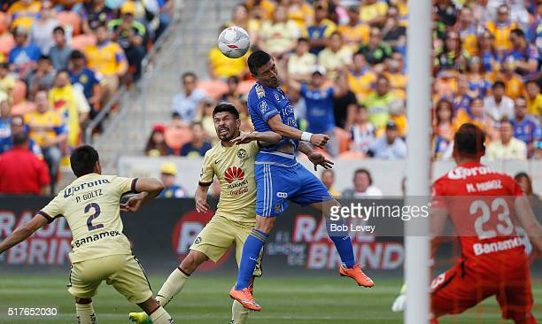 Hector Mancilla of Tigres UANL heads the ball as he his pressured by Oribe Peralta of Club America in the first half at BBVA Compass Stadium on March...