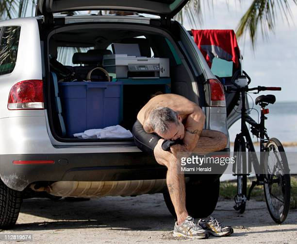 Hector Picard of Pompano Beach uses his teeth to put on his socks before he begins his training for a triathlon on Key Biscayne September 17 2009