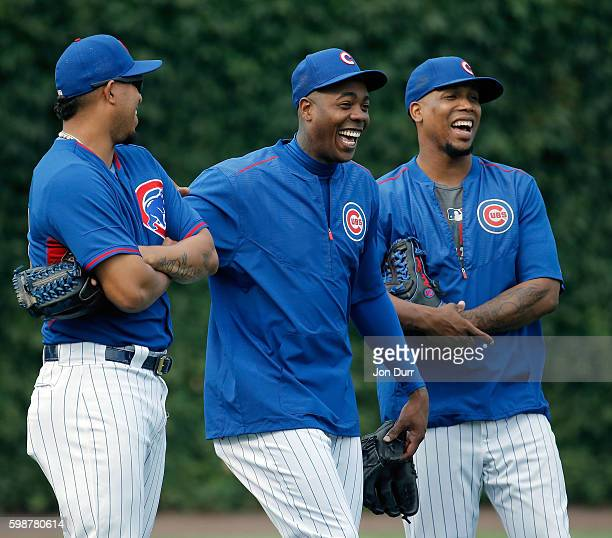 Hector Rondon of the Chicago Cubs Aroldis Chapman and Pedro Strop laugh while having a conversation during warmups before the game against the...