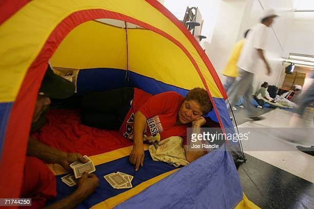 Hector Rosado and Rachel Rodriguez play a game of cards in the tent they erected inside the Booker T Washington Senior High School Red Cross...