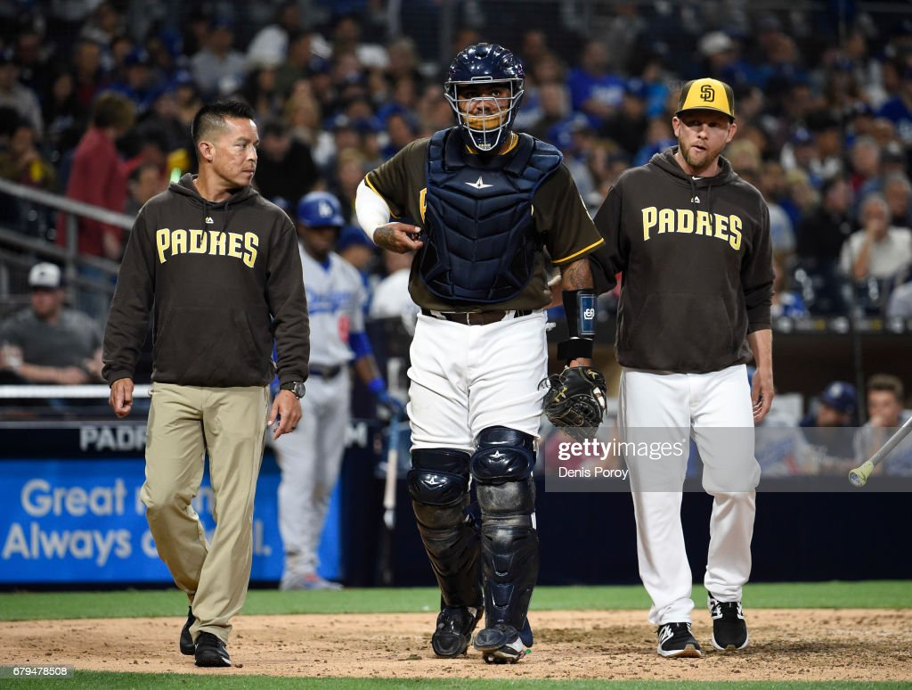Hector Sanchez #44 of the San Diego Padres, center, leaves the game with Andy Green, right, and an unidentified trainer during the sixth inning of a baseball game against the Los Angeles Dodgers at PETCO Park on May 5, 2017 in San Diego, California.