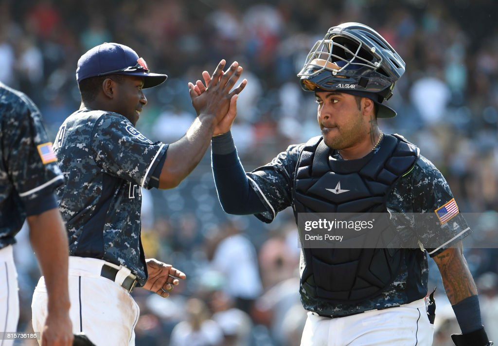 Hector Sanchez #44 of the San Diego Padres, right, and Jose Pirela #2 high five after beating the San Francisco Giants 7-1 in a baseball game at PETCO Park on July 16, 2017 in San Diego, California.
