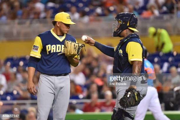 Hector Sanchez of the San Diego Padres talks to starting pitcher Dinelson Lamet during the first inning against the Miami Marlins at Marlins Park on...
