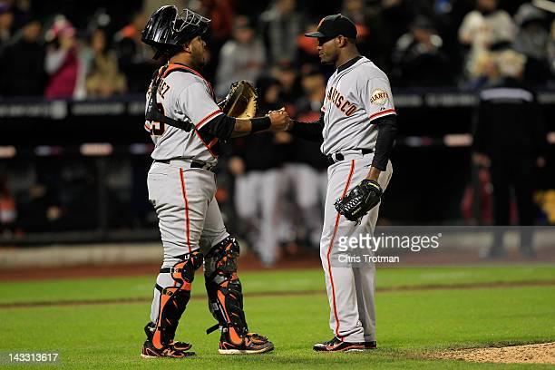Hector Sanchez of the San Francisco Giants congratulates Santiago Casilla of the San Francisco Giants for pitching in the ninth inning and securing...