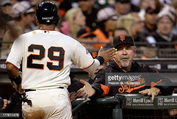 Hector Sanchez of the San Francisco Giants is congratulated by manager Bruce Bochy after Sanchez scored on a wild pitch in the fifth inning against...