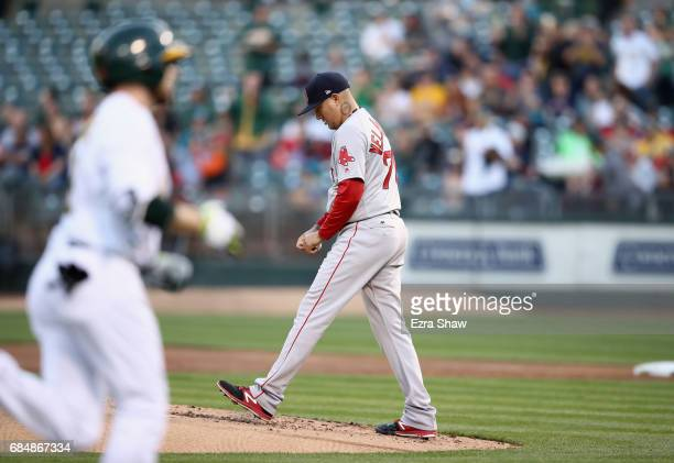 Hector Velazquez of the Boston Red Sox reacts after giving up a home run to Jed Lowrie of the Oakland Athletics in the first inning at Oakland...