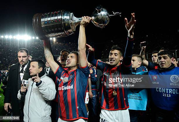 Hector Villalba and Gonzalo Veron of San Lorenzo celebrate with the trophy after winning the Copa Libertadores during a second leg final match...