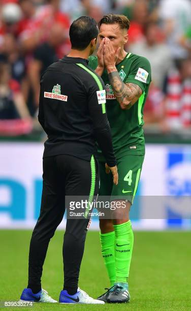 Hed coach Alexander Nouri talks with Robert Bauer of Bremen after the Bundesliga match between SV Werder Bremen and FC Bayern Muenchen at...