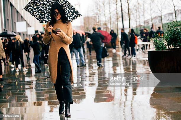 Hedvig Opshaug checks her phone holds a floral umbrella and wears a long Alexander Lewis Mayim Turtleneck sweater during London Fashion Week...