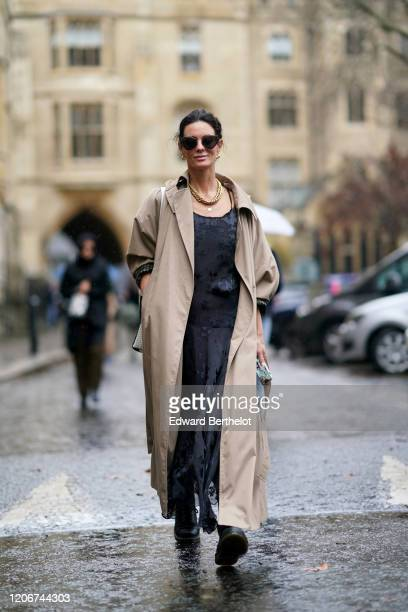 Hedvig Opshaug wears sunglasses, a beige trench coat, a black lace mesh dress with floral embroidery, a golden necklace, during London Fashion Week...