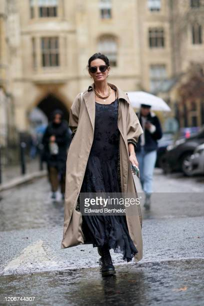 Hedvig Opshaug wears sunglasses a beige trench coat a black lace mesh dress with floral embroidery a golden necklace during London Fashion Week Fall...