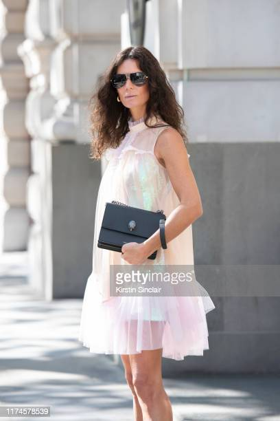 Hedvig Sagfjord Opshaug wears Givenchy sunglasses, Bora Aksu dress and a Kurt Geiger bag on September 13, 2019 in London, England.