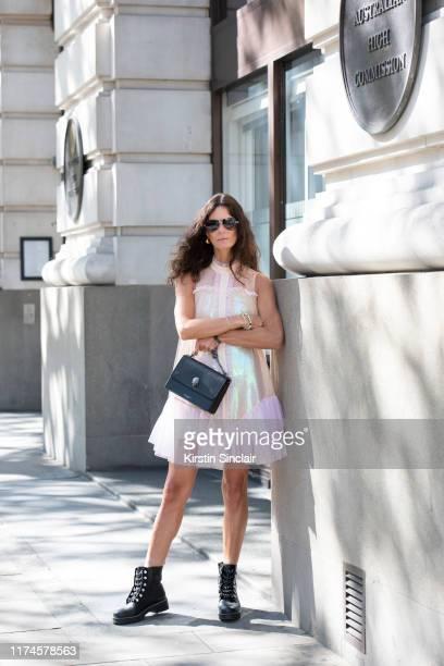 Hedvig Sagfjord Opshaug wears Givenchy sunglasses, Bora Aksu dress and Kurt Geiger boots and bag on September 13, 2019 in London, England.