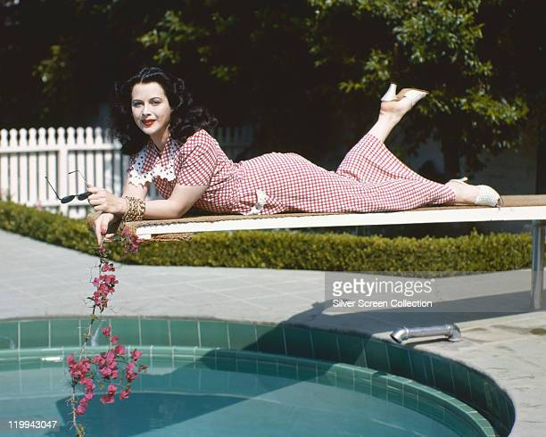 Hedy Lamarr Austrian actress wearing a red gingham dress and holding a branch with pink flowers while leaning front down on a diving board over the...