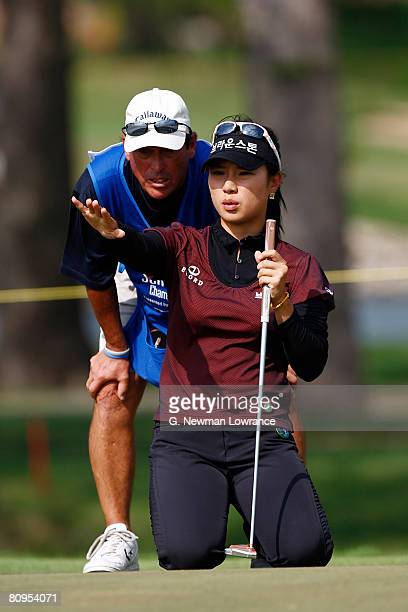 Hee Young Park of South Korea discusses a putt with her caddie on the 14th hole during the first round of the SemGroup Championship presented by John...