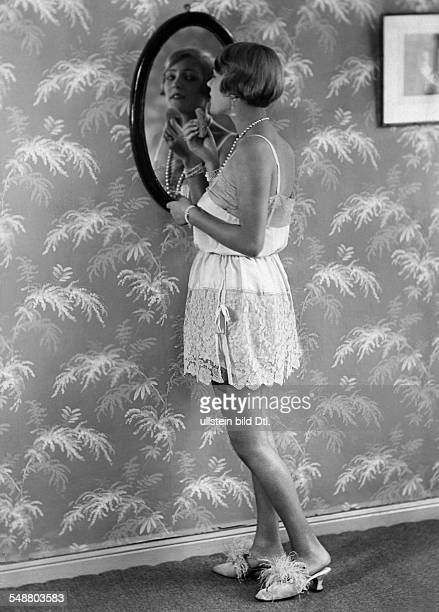 Heel, Ellen - Actress - full-figure portrait - Series: From morning until midnight, in a full slip with lace at the mirror - 1925 - Photographer:...