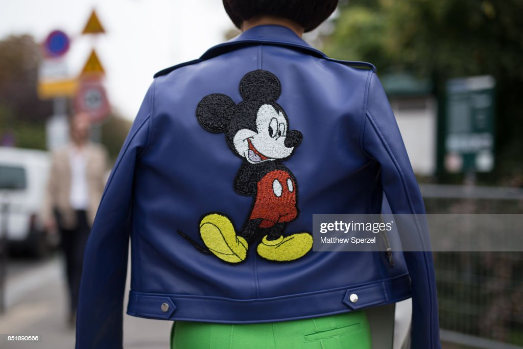 Heewon Kim is seen attending Lanvin during Paris Fashion Week wearing a blue leather Mickey Mouse jacket with green outfit on September 27, 2017 in Paris, France.