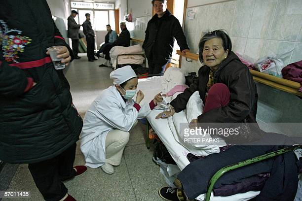 Nurse treats a patient in a hospital bed in a crowded corridor of the Anhui Provincial Hospital in the capital Hefei, 24 February 2006. Chinese...